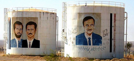 Oil tanks near the Syria-Iraq border decorated with pictures of past and present Syrian leaders. (photo: Richard Messenger)