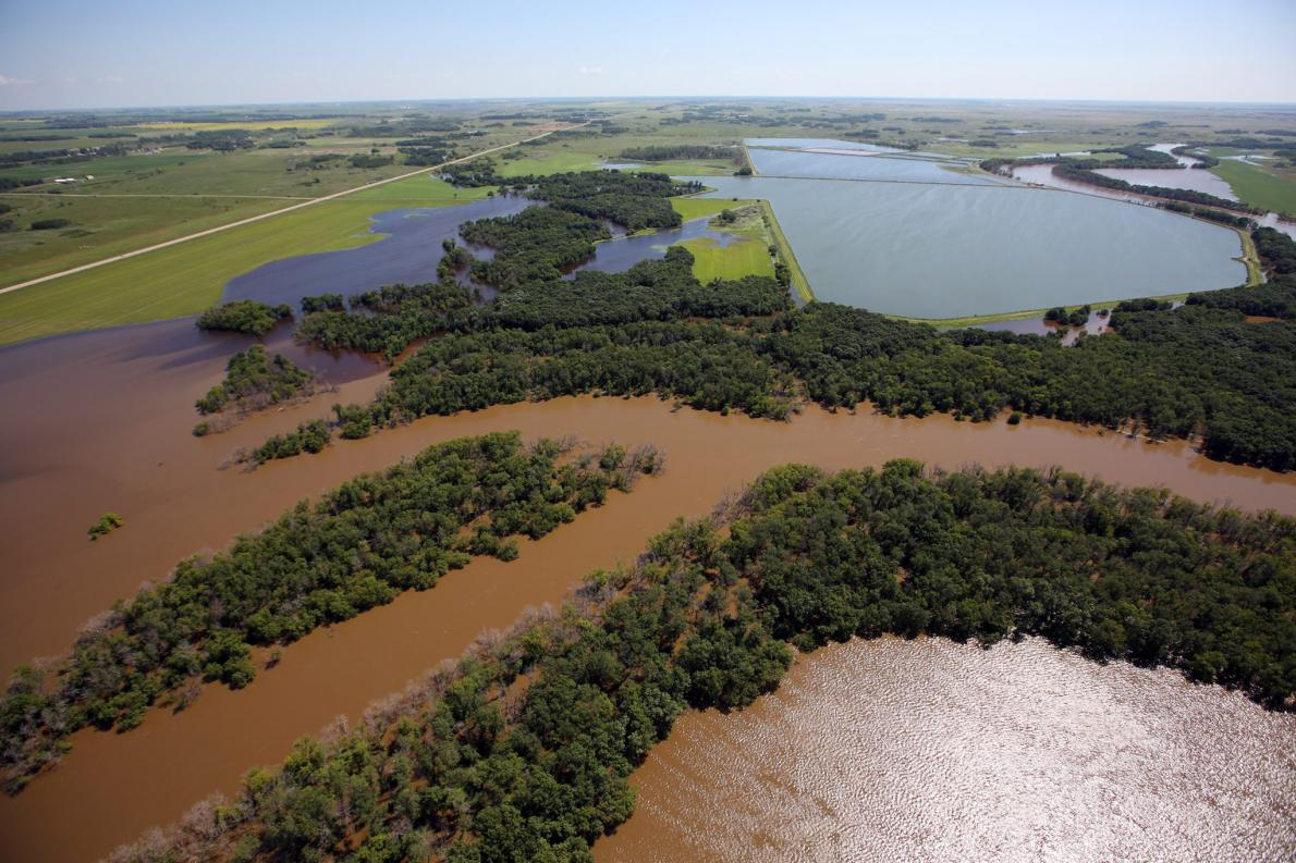 Climate change plus local land use worsened prairie flooding in parts of Canada, according to a new scientific report.  In this July, 2014 photo, the swollen Assiniboine River covers farmland in Manitoba, Canada. (photo: Tim Smith, The Canadian Press/Associated Press )